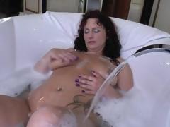 Aged in a soapy bathtub masturbates solo