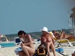 Exposed older wife acquires a stranger to rub sun lotion on her back, tiny melons and little hair visible.